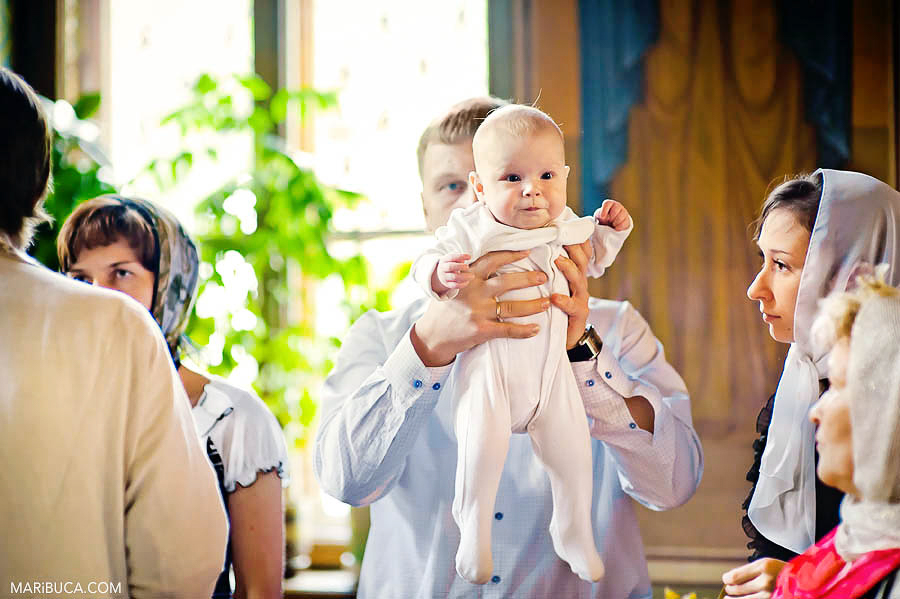 The dad holds baby girl in the orthodox christening church in the San Francisco