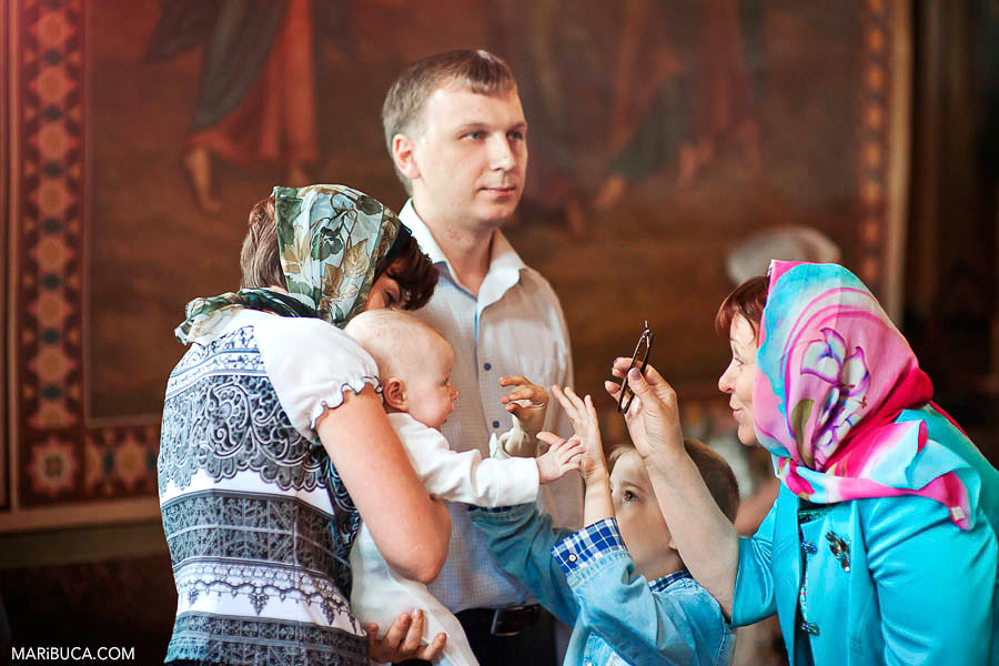 The grandmother and a little girl play with baby girl during Baptism ceremony in the SF church.