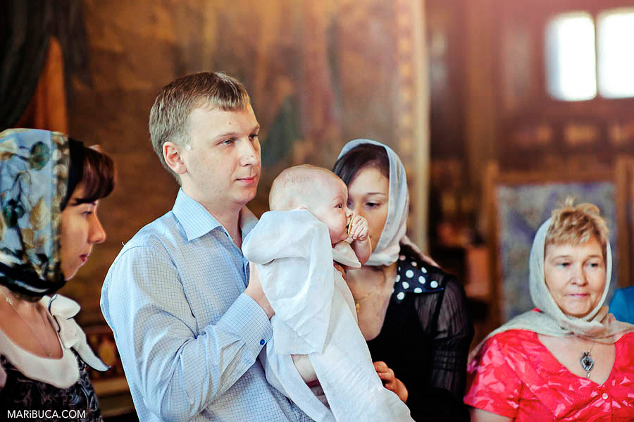 The father holds the baby daughter in the church