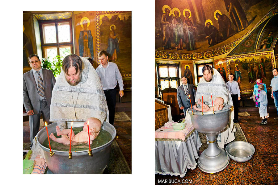 The pastor immersing baby in the water in the Orthodox church