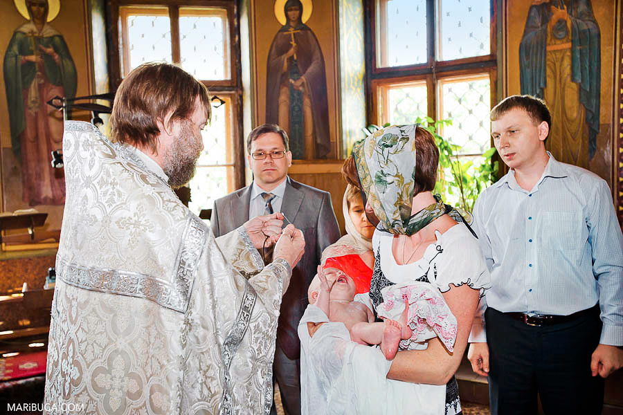 The priest put on the cross in the baby. The godmother holds baby and the baby girl is crying.