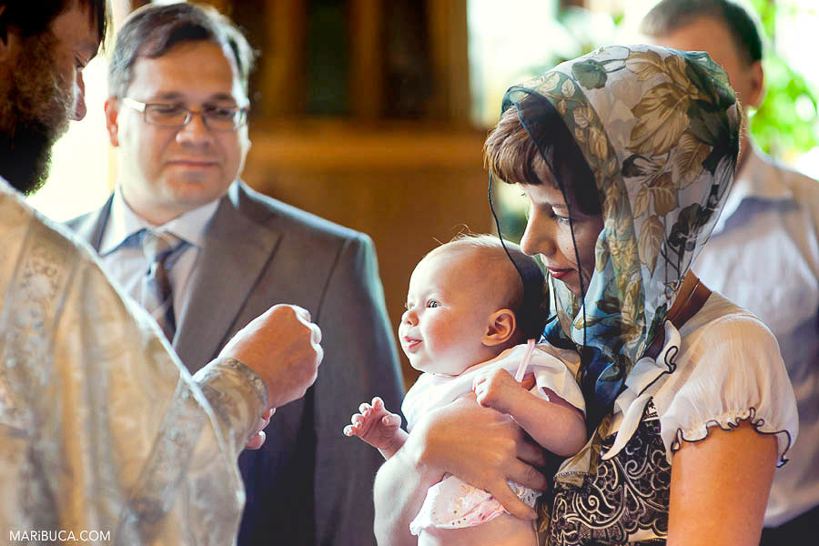 Infant is looking to the priest.
