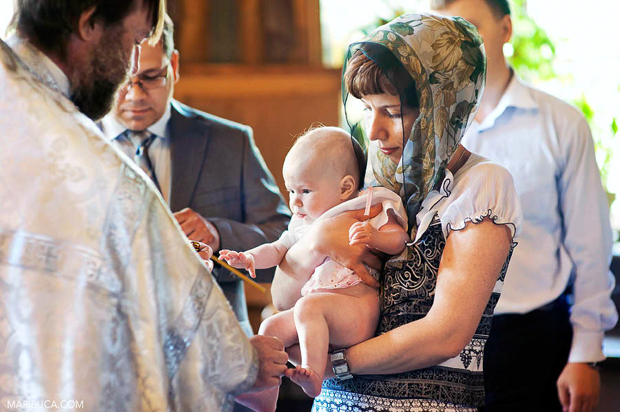 The godmother holds the little baby girl in the christening church in the San Jose.