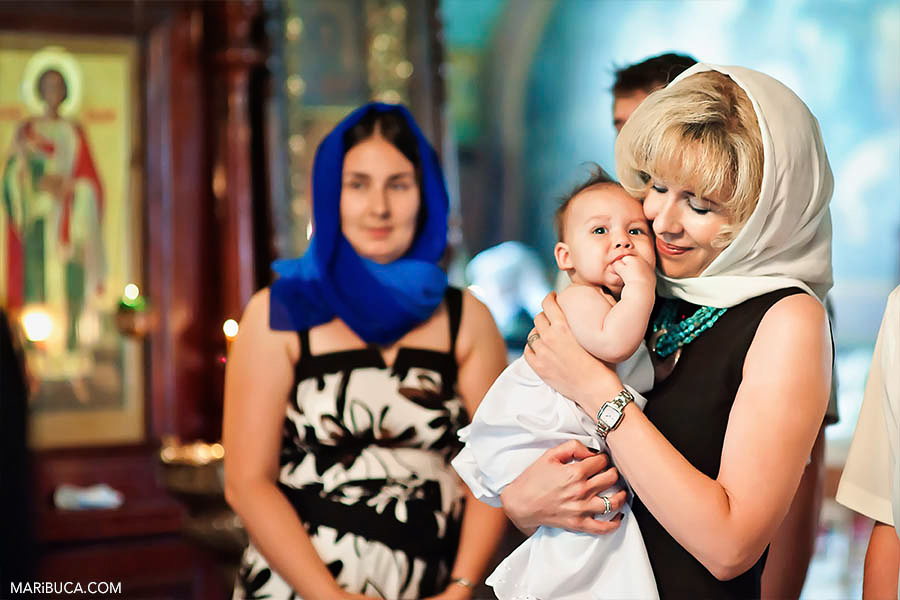 Godmother holds godson's son during christening in the church