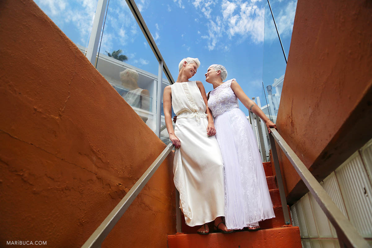 Two brides with white and ivory dress stay in the staircases and looking each other