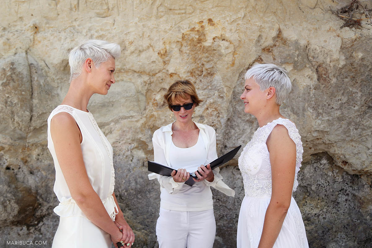 Wedding ceremony of two girls in white dresses where the officiant registers their marriage on Cowell Beach in Santa Cruz
