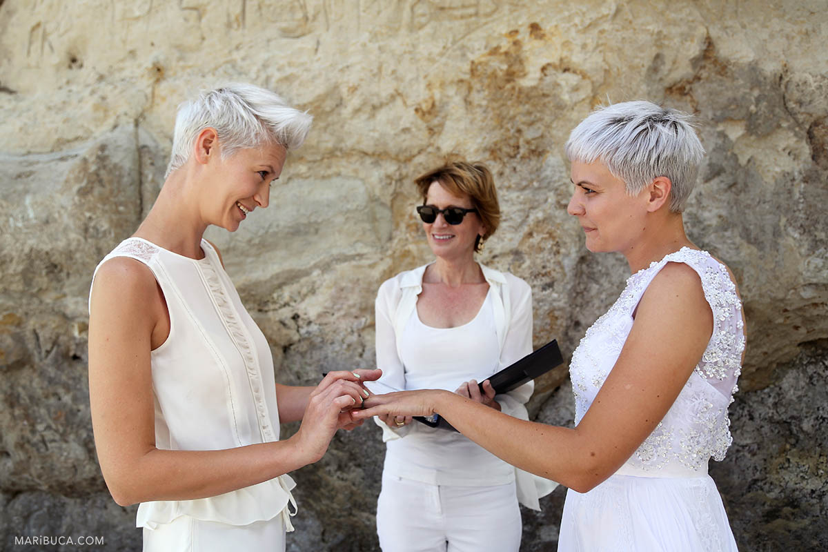 Two brides with white dresses exchange wedding rings in the Santa Cruz beach.