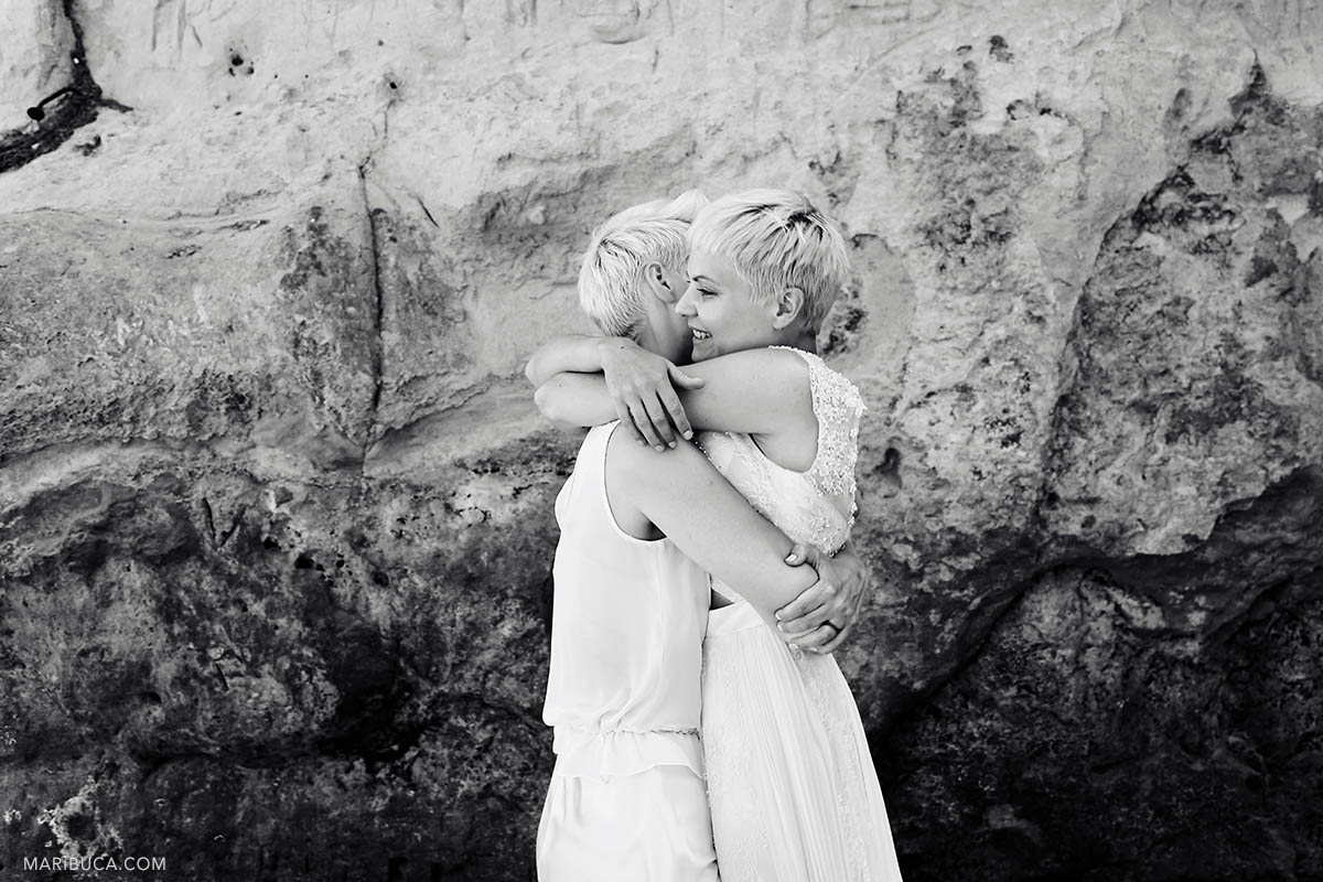 Black and white image of two brides. They hug and congrats each other after wedding ceremony in the mountain background.