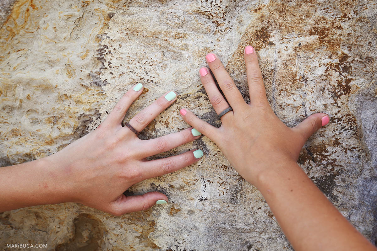 hands of the brides with wedding rings made of stones and light pink - light green manicure on the hands of girls.