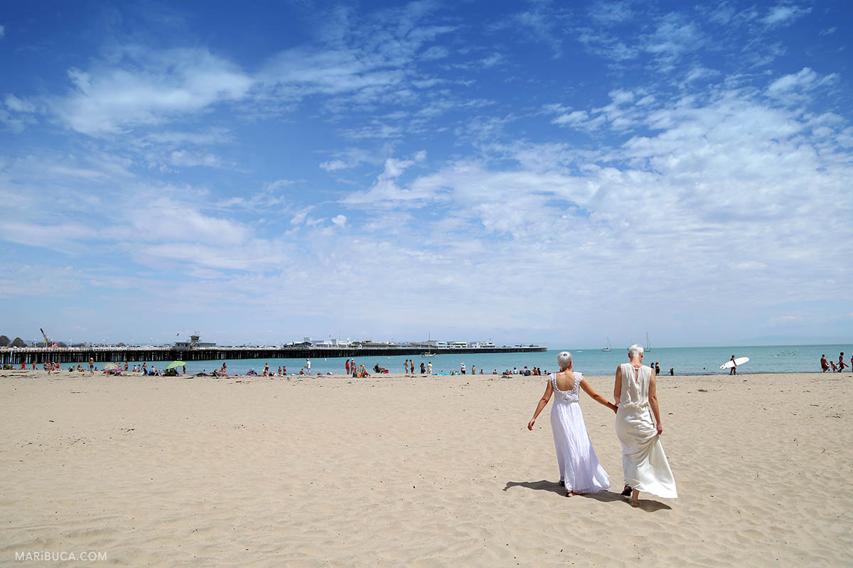 Brides walking in the Cowell beach after their wedding ceremony in the Santa Cruz