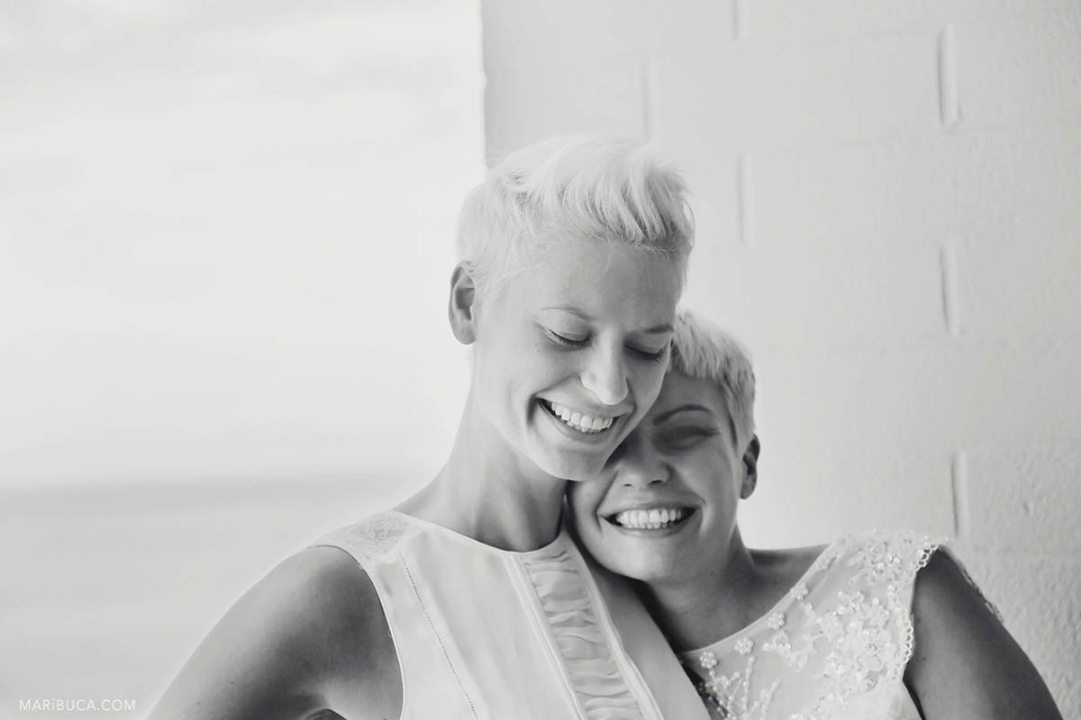Black and white image with two portraits of brides hug each other and laughing after wedding ceremony. Just married!