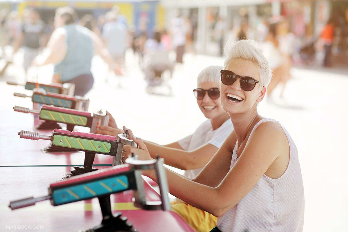 girls with short haircuts, sunglasses and white T-shirts in an amusement park are laughing, Santa Cruz.