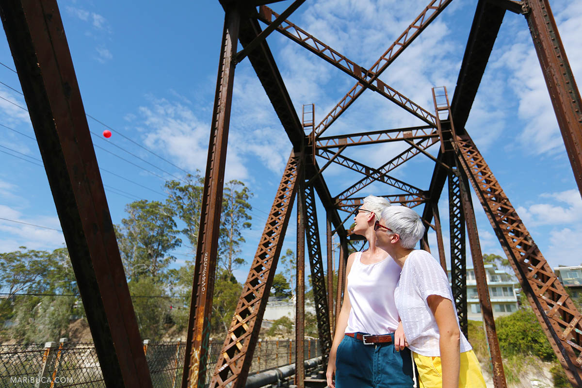 girl with short hair wearing sunglasses watches as the flies red ball on a background of rusty iron railway bridge and blue sky in the Boardwalk amusement park.