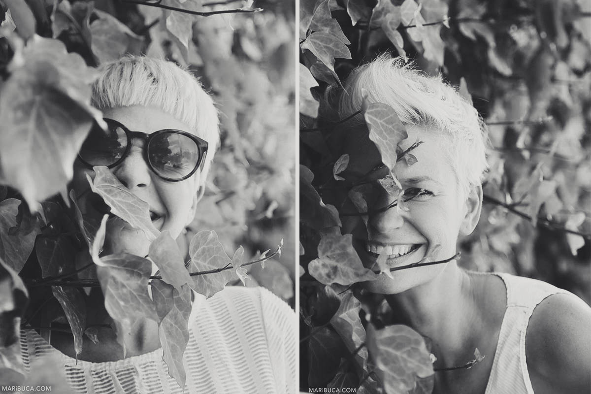 Black-and-white photography of a portrait of girls laughing and having fun in the bushes with leaves.