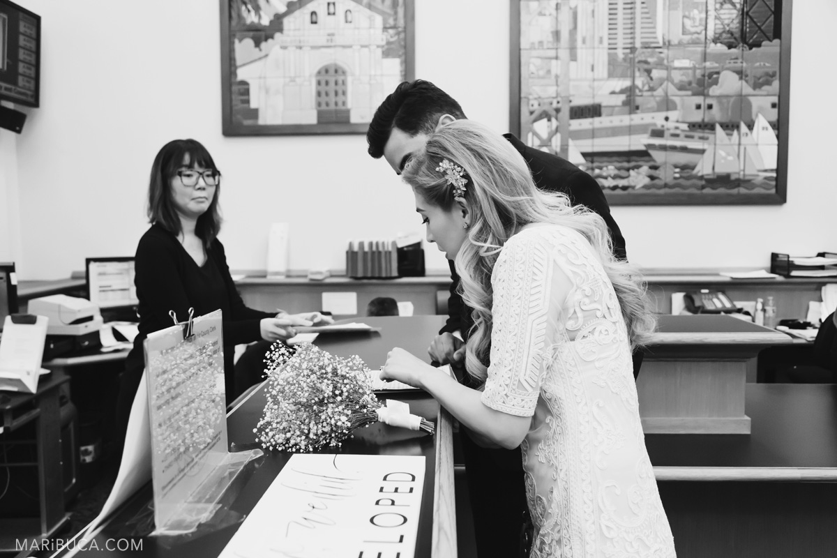 The bride and groom sign the document marriage license in the register office SF City Hall.
