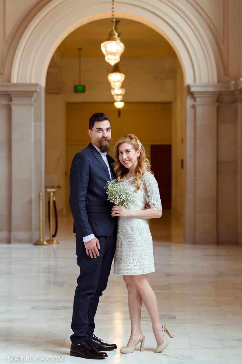 Romantic couple: the bride and groom stand in an embrace against the background of the arch in the SF City Hall in San Francisco