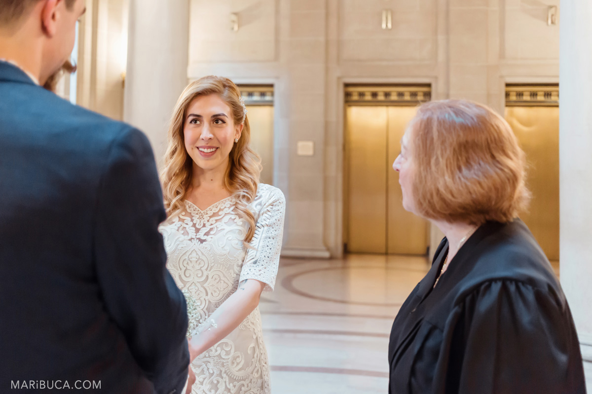 The bride looks into the groom eyes and the officiant looks to the bride during the wedding ceremony in San Francisco city hall.