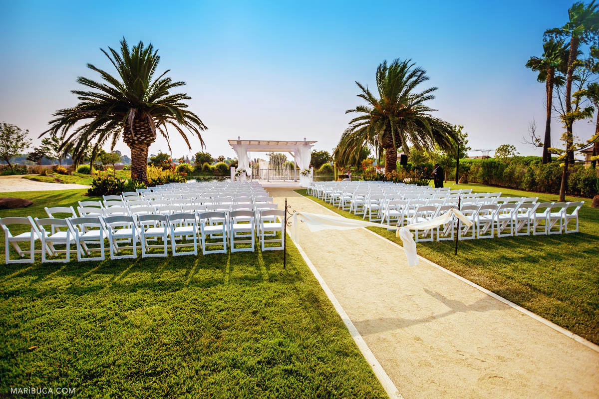 Outdoor wedding ceremony in the Newberry Estate Vineyards. The weather is perfect! Blue sky, white chairs around and sands road. Everything set up for the wedding ceremony in the Sunny California.