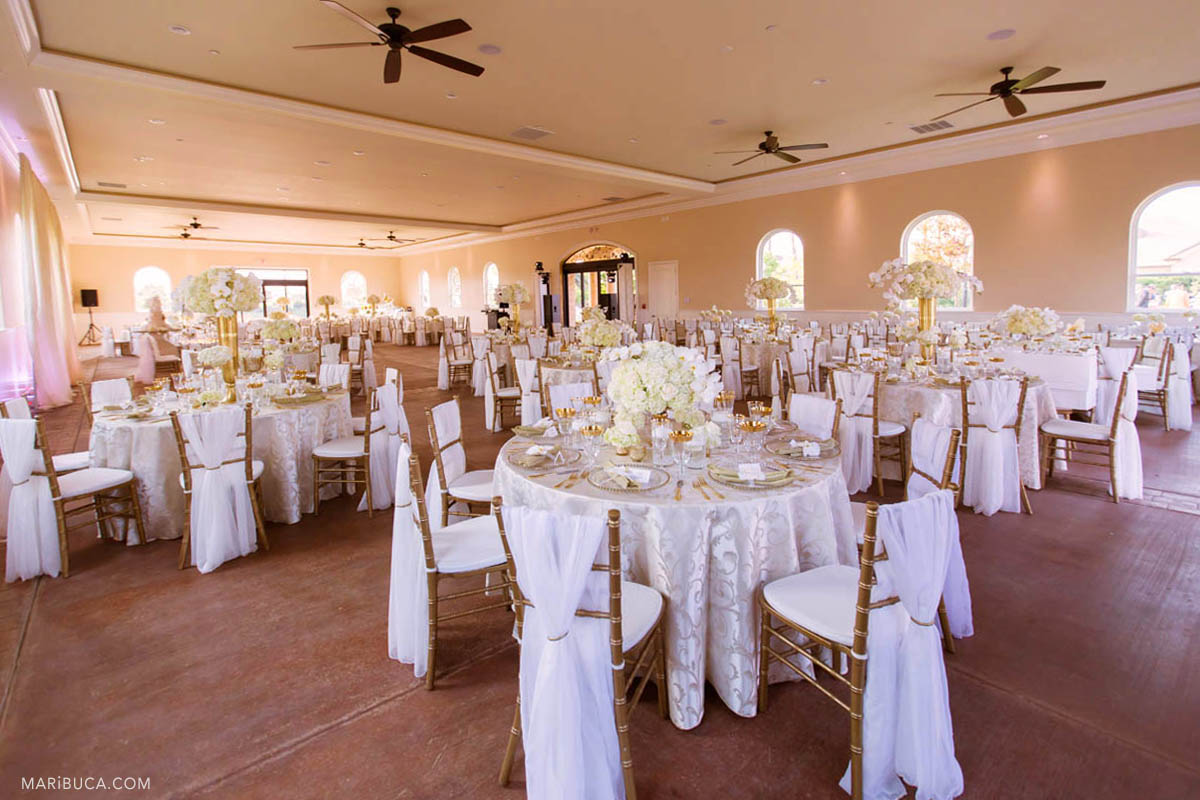 Wedding reception detail: rounded white tables, white flowers. Indoor in the Newberry Estate Vineyards