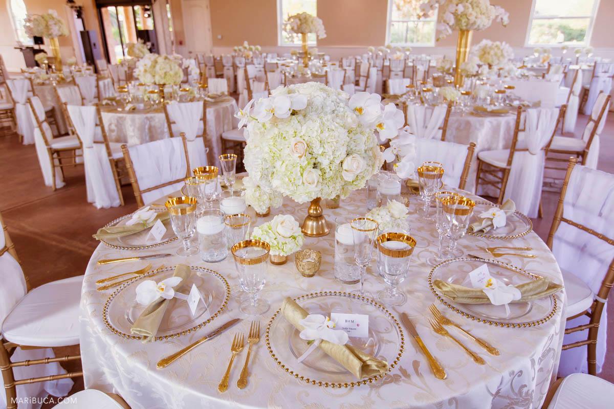 Reception details with white tablecloth and flowers, golden silvers and white flowers