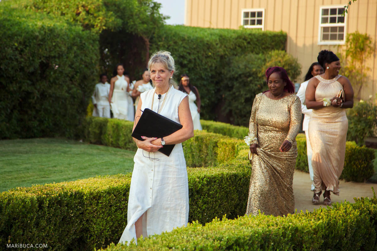 Reception is starting and officiant, bridesmaids are going down the aisle in the Newberry Estate Vineyards.
