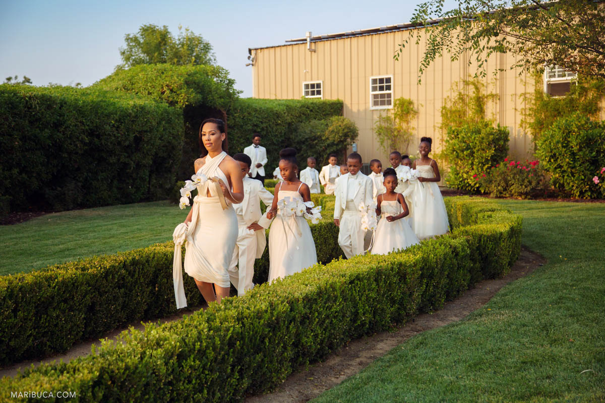Ceremony is starting and bridesmaids with flower girl and Barrier Rings are going down the aisle in the Newberry Estate Vineyards.