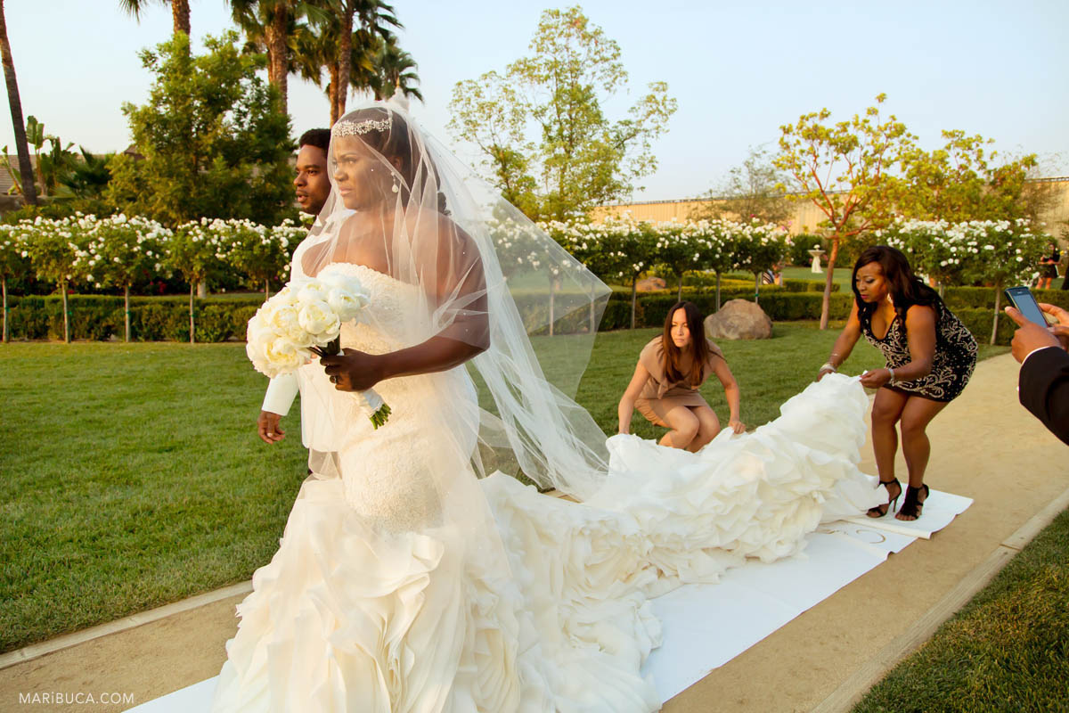Adorable bride wearing Vera Wang white long fabulous wedding dress and her friend help her with them.