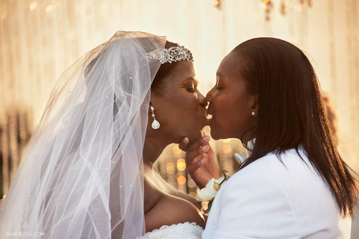 Two brides have the first kiss as married couple in their wedding ceremony..