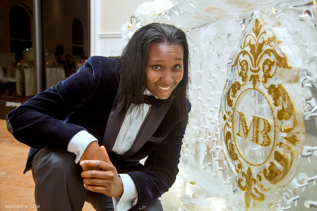 The groom girl in the dark velvet jacket smile next to the ice bar with golden sign MB