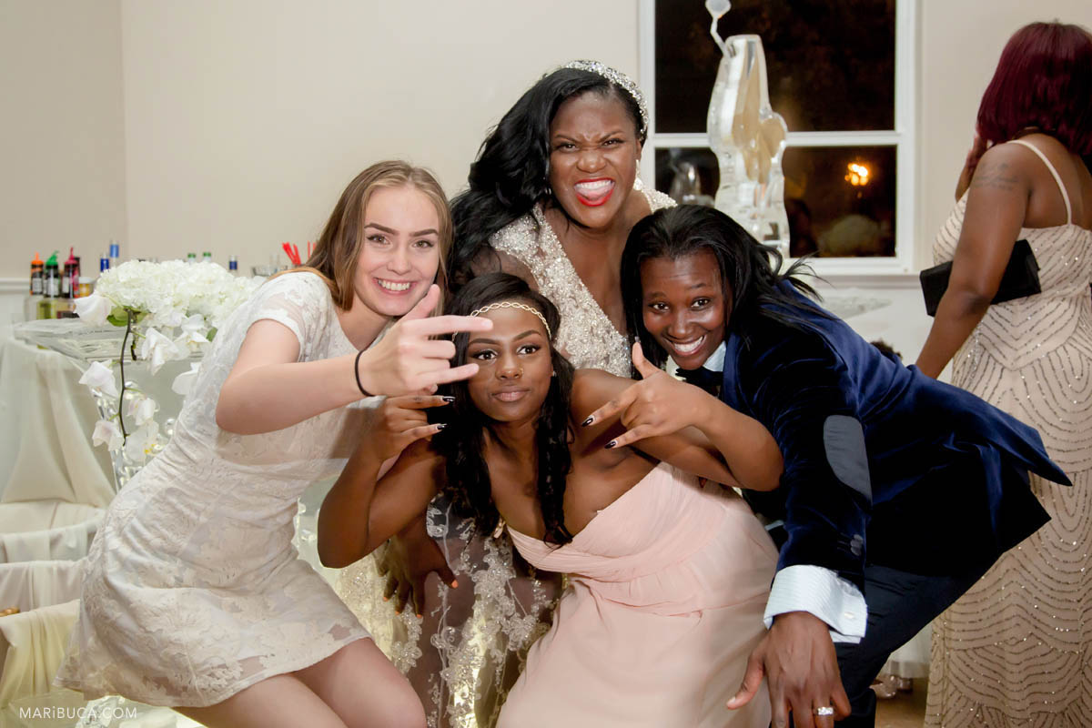 Bride, groom and guests are doing gangster posing for pictures in the indoor wedding