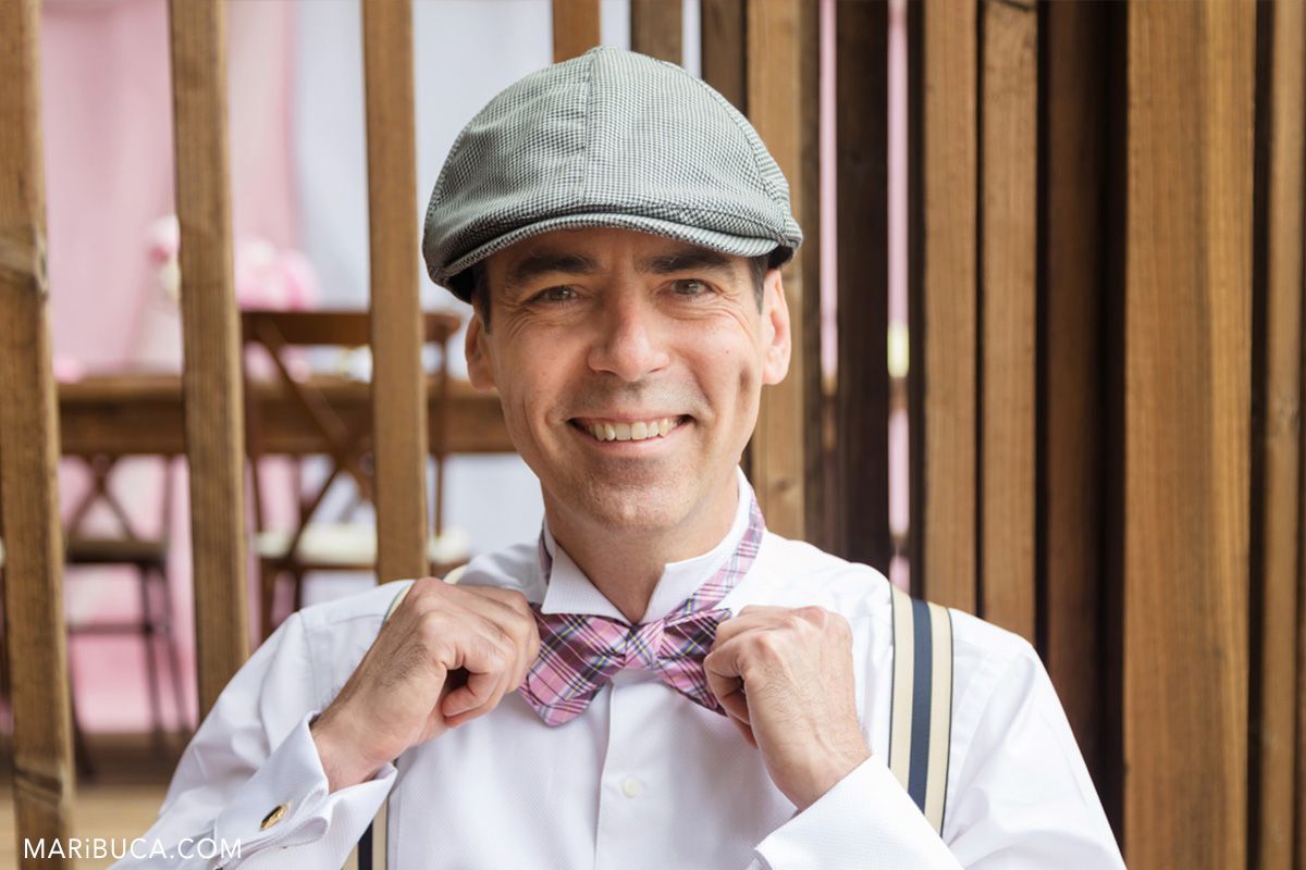 The groom smile and hold it his pink bow. He wears light black hat and white shirt in the getting ready.