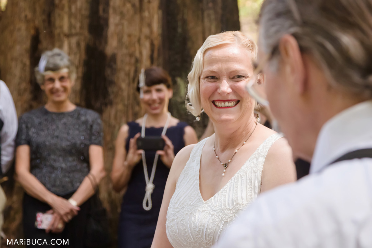 The bride is smiling, crying and looking at the wedding officiant.