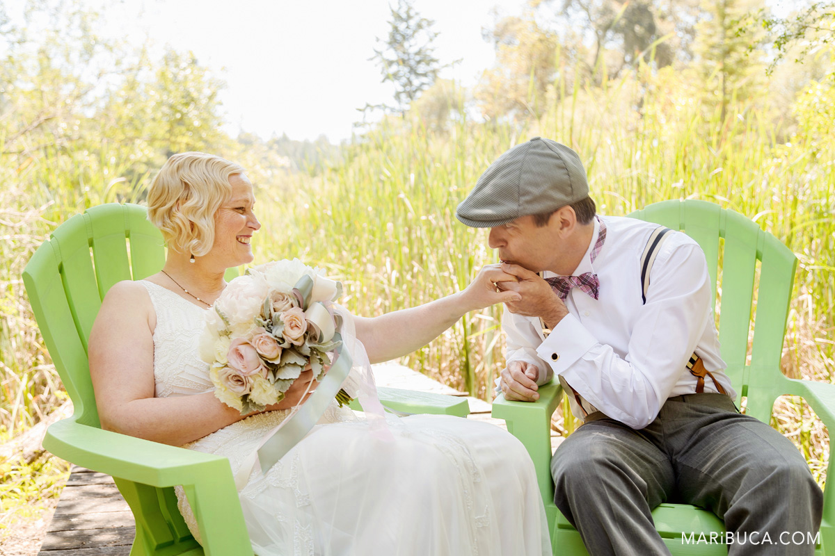 The groom kisses the bride's hand after the ceremony and they sit in the light green comfy chairs and high grass surrounded.