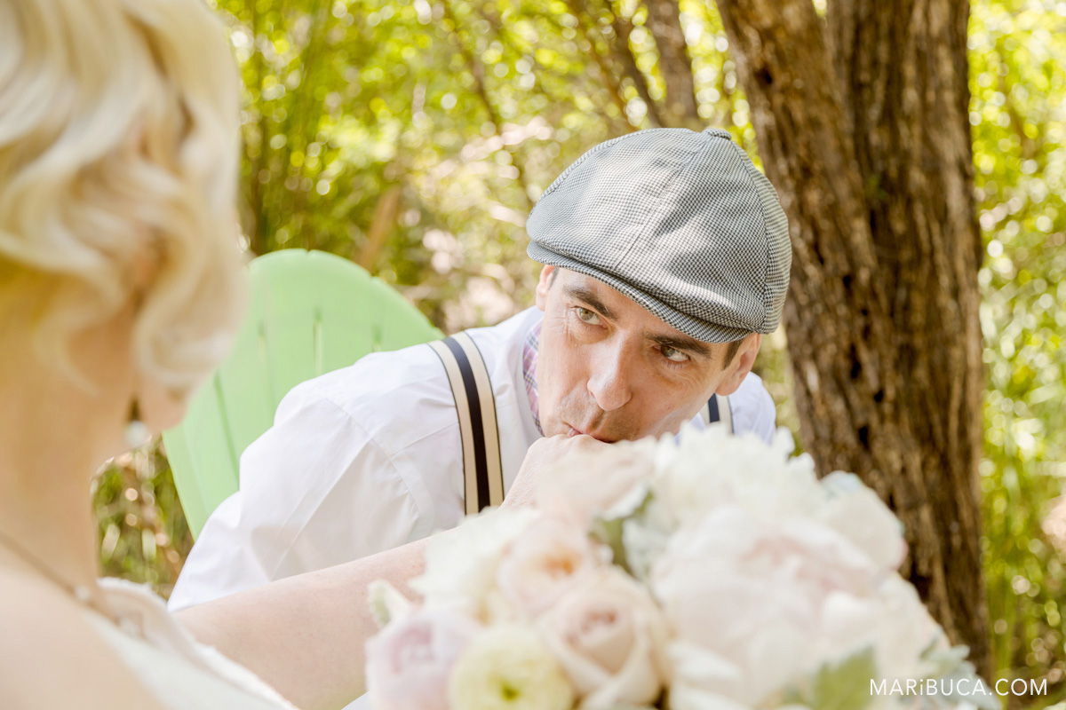 The groom is looking at the bride and kissing her hand surrounded the trees in the sunny day..