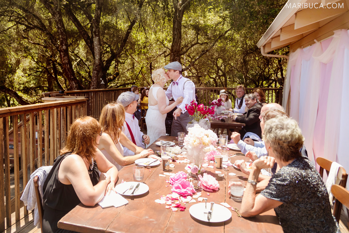 Outdoor wedding reception. Guests are looking at the bride and groom. Newlyweds are kissing.