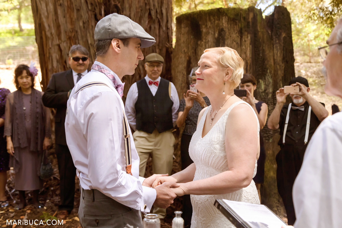 The bride and the groom are looking each other during the wedding vows.
