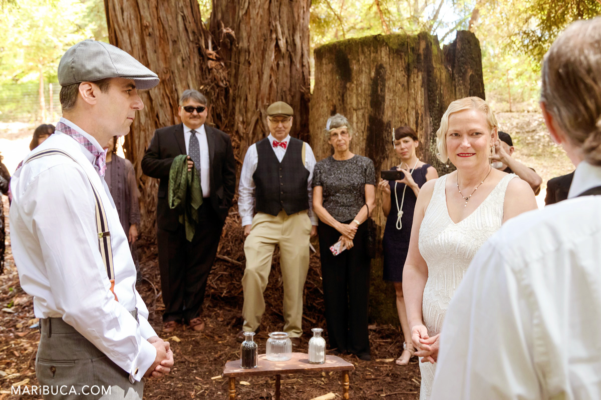 Outdoor wedding ceremony in the Los Gatos where the bride and the groom are listening wedding officiant in the park in the Los Gatos.