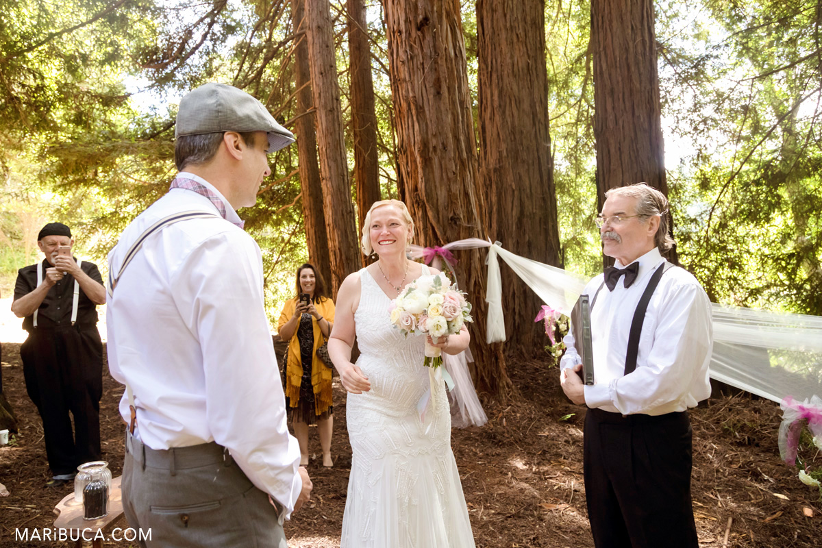 The bride is looking at the groom and smiling during wedding ceremony in the wood.
