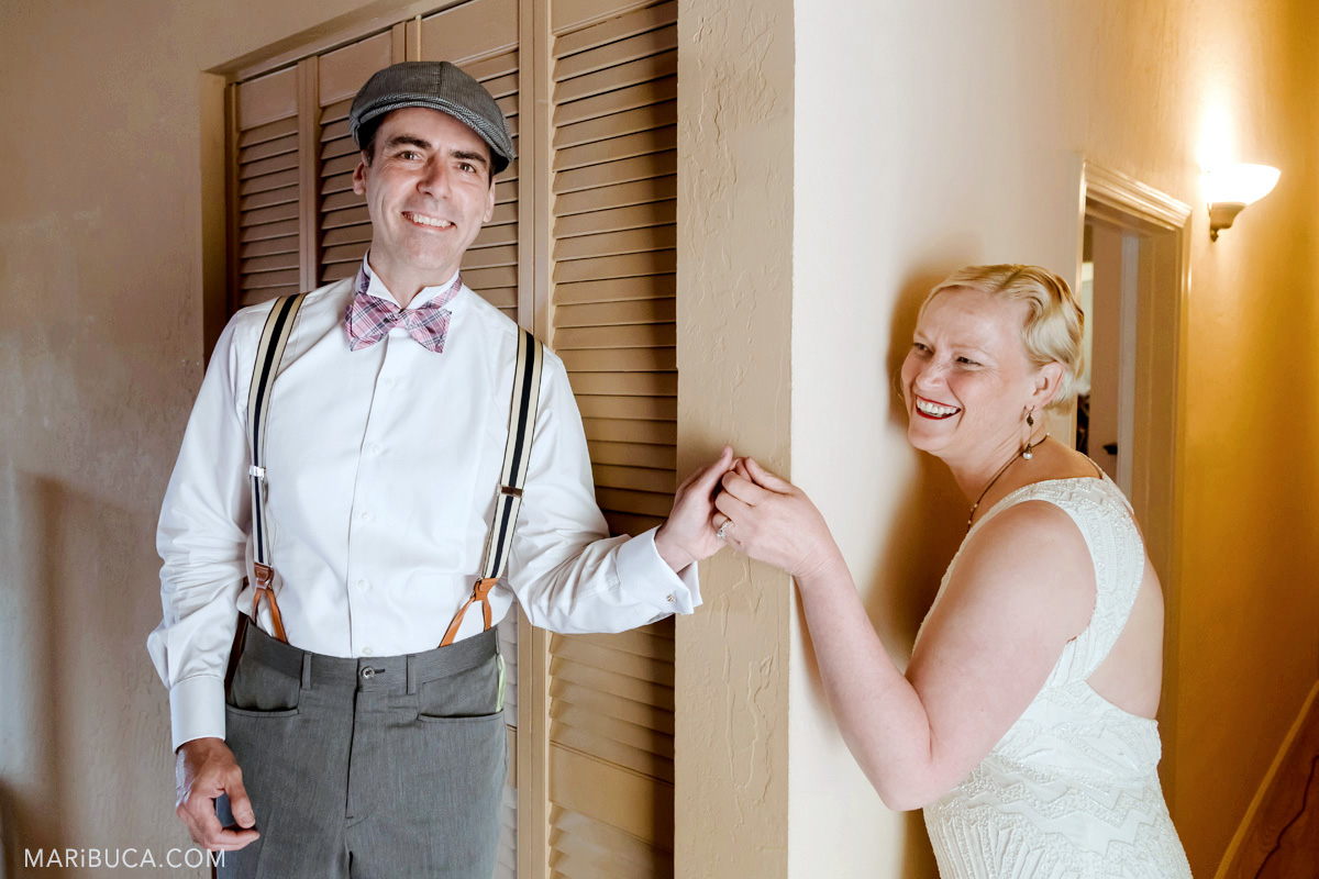 the groom and the bride smile during indoor first look and 1920s theme wedding.
