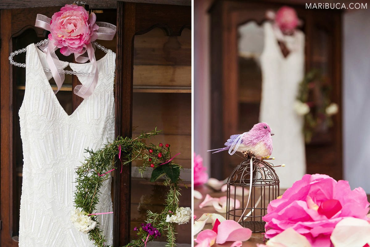 Wedding detail: The white wedding dress, pink flowers and bird decoration.