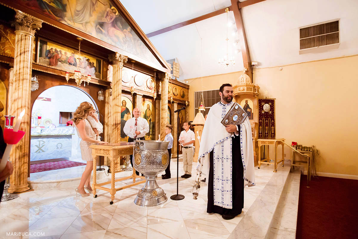 The priest stays with the smoke candle in Greek church as part of orthodox traditional during the christening the baby girl.