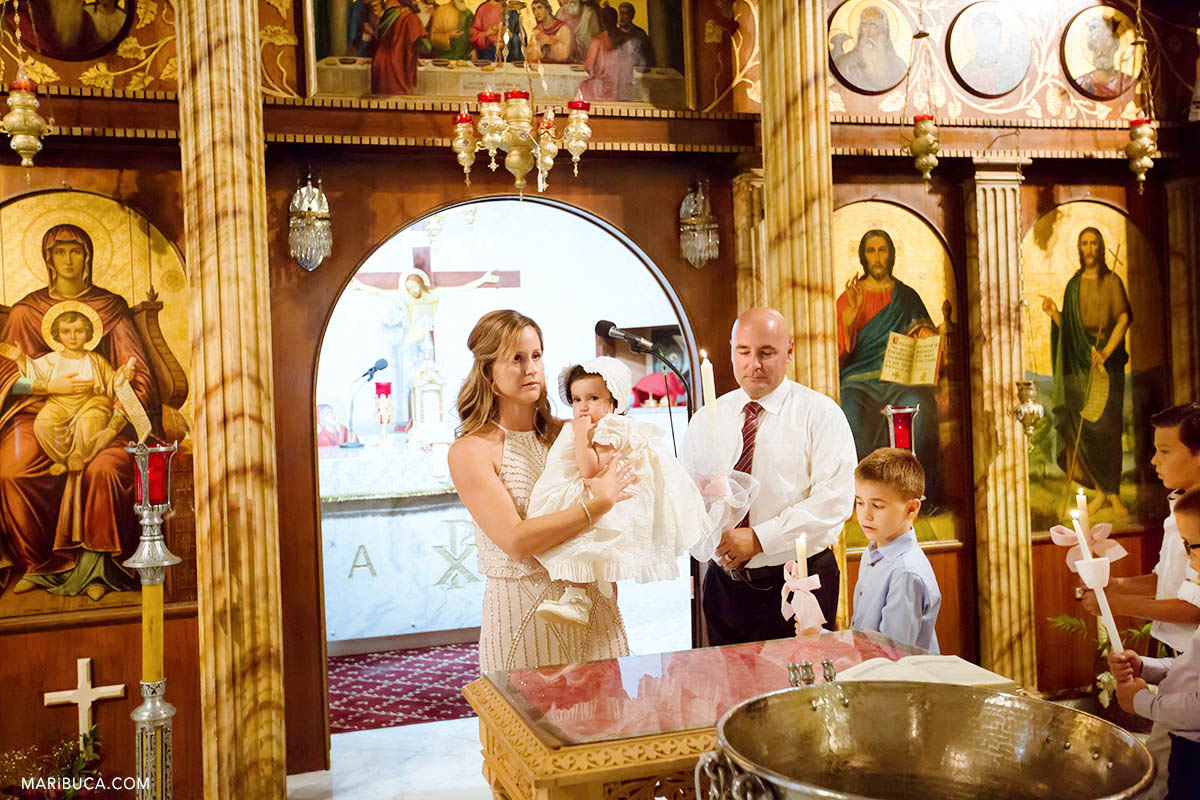 The godmother and the godfather with stand with goddaughter in the church.