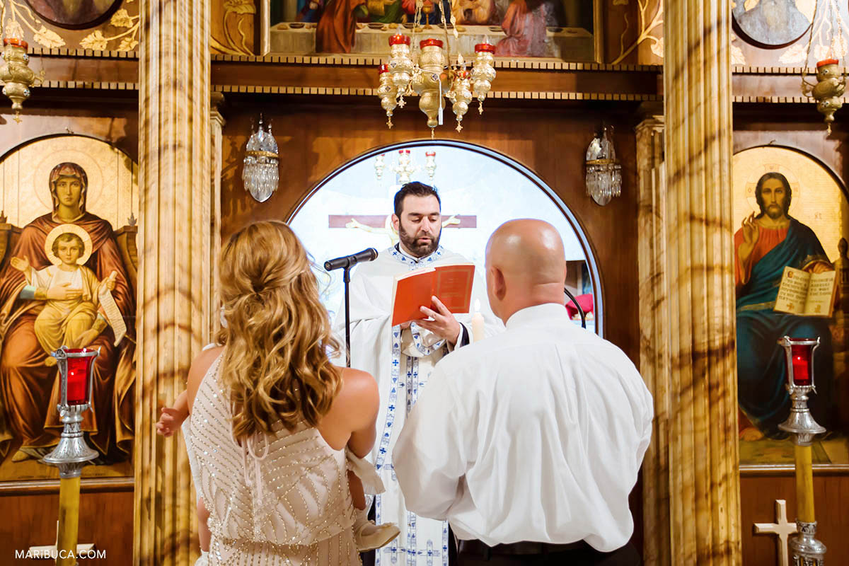 The priest read the part from the bible for godmother and godfather during Greek Orthodox Baptism.