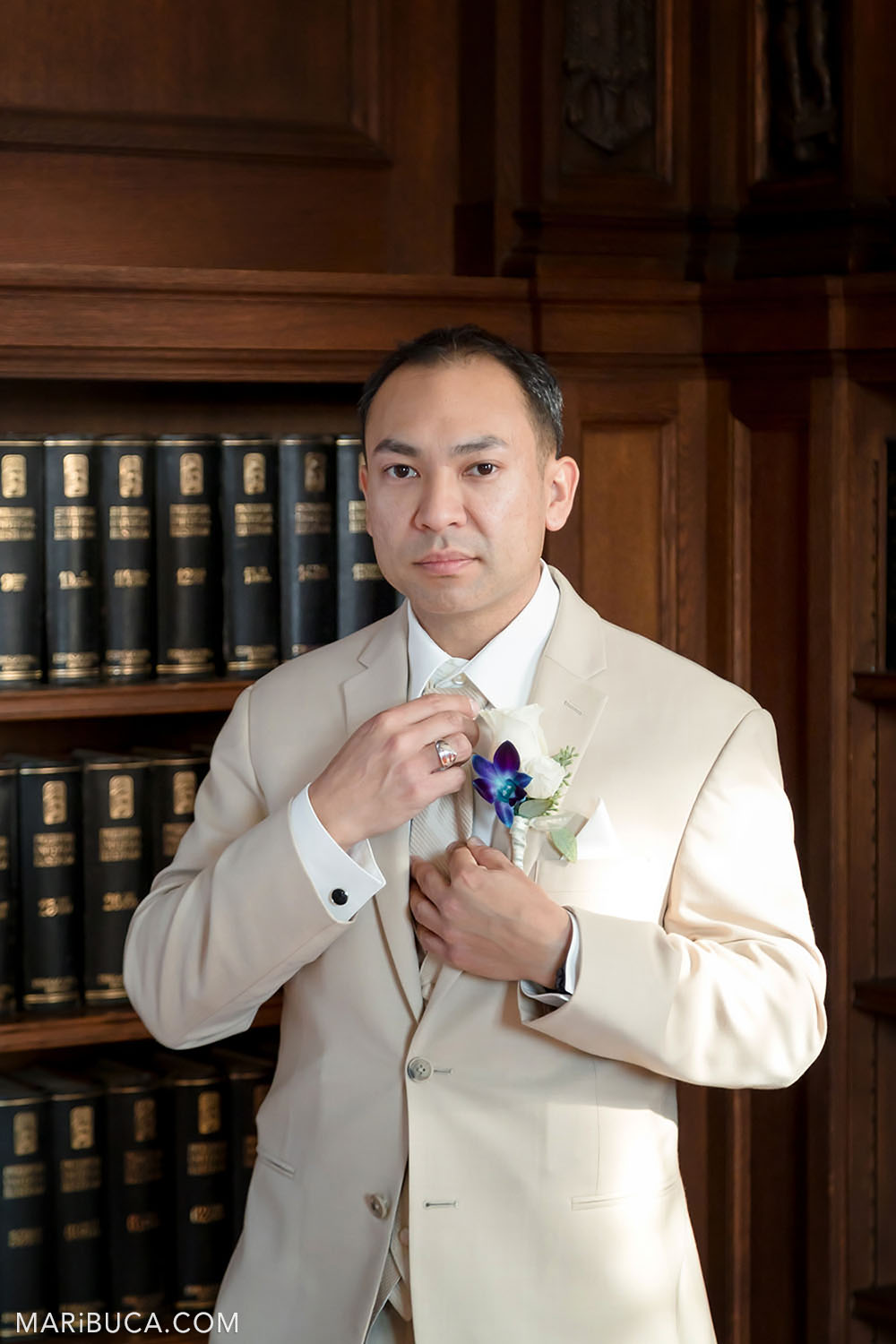 The groom holds his tie and wears light beige wedding suit during getting ready in the Library, Kohl Mansion, Burlingame