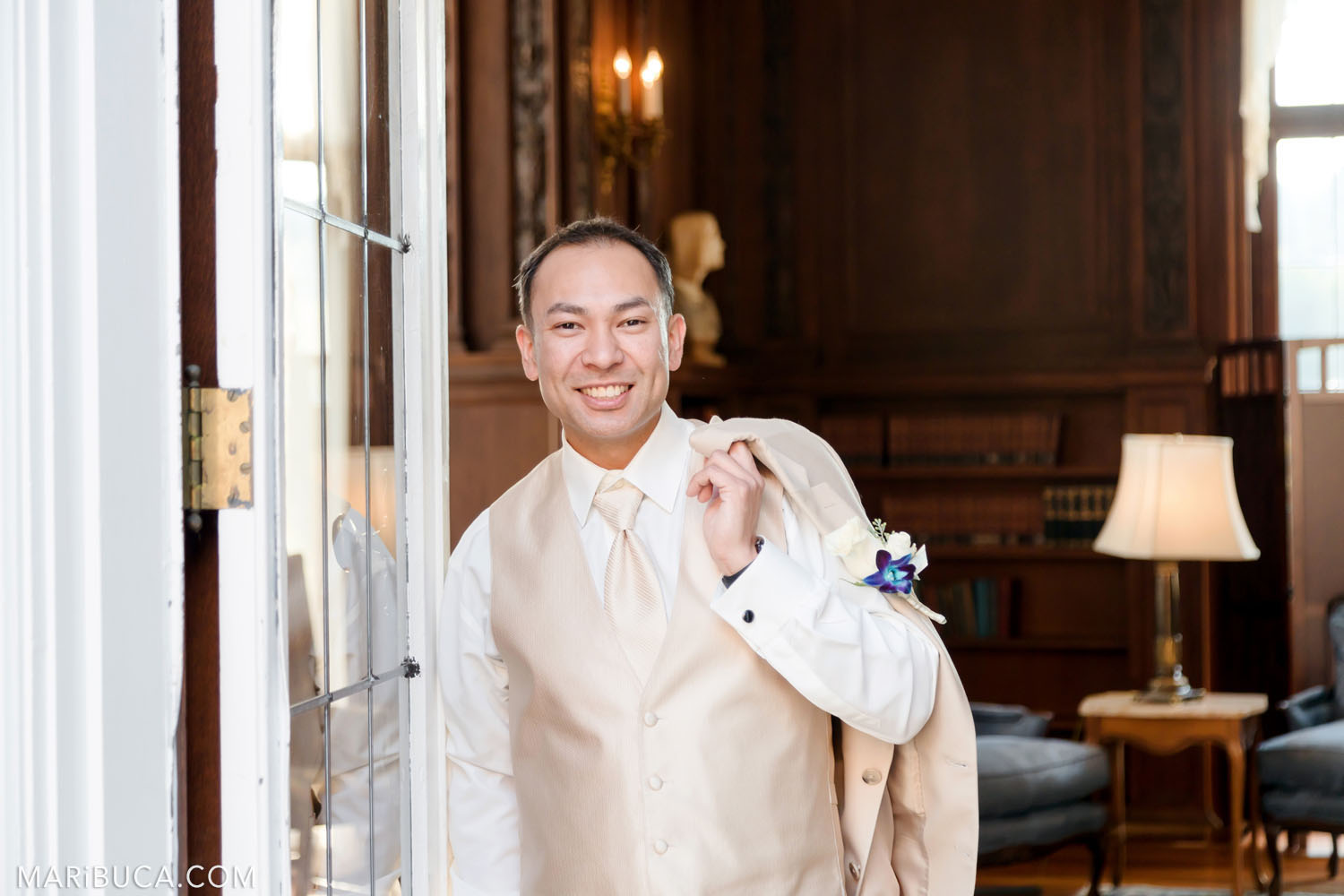The groom holds wedding light beige jacket through the shoulder and stays in the Library, Kohl Mansion, Burlingame