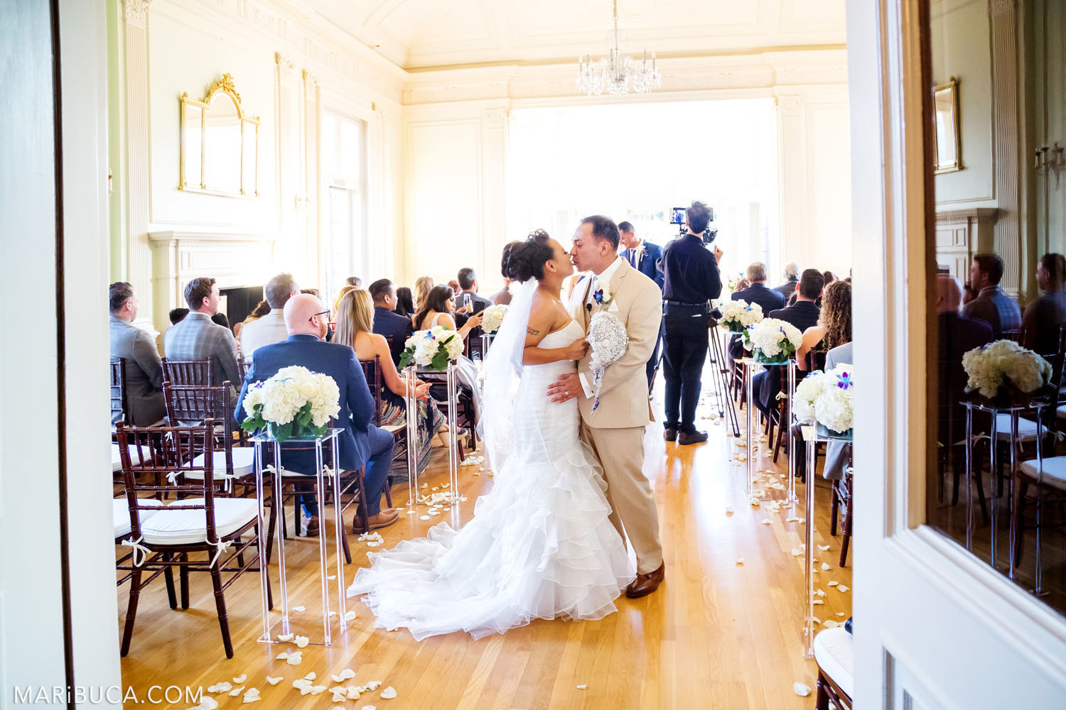 The bride and the groom kiss each other before leaving the Dining room, Kohl Mansion Wedding, Burlingame.