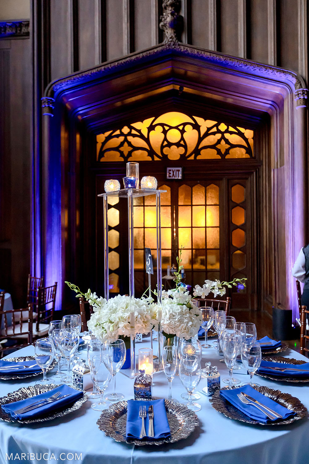 Fabulous venue with rounded light blue table, white bouquets of flowers on it with purple and orange lights in the Great Hall, Kohl Mansion, Burlingame
