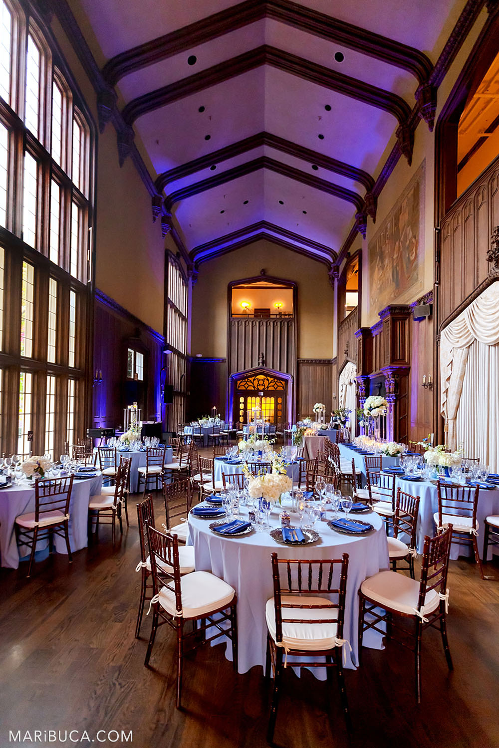 Beautiful venue with rounded light blue tables, high ceilings with purple lights in the Great Hall, Kohl Mansion, Burlingame