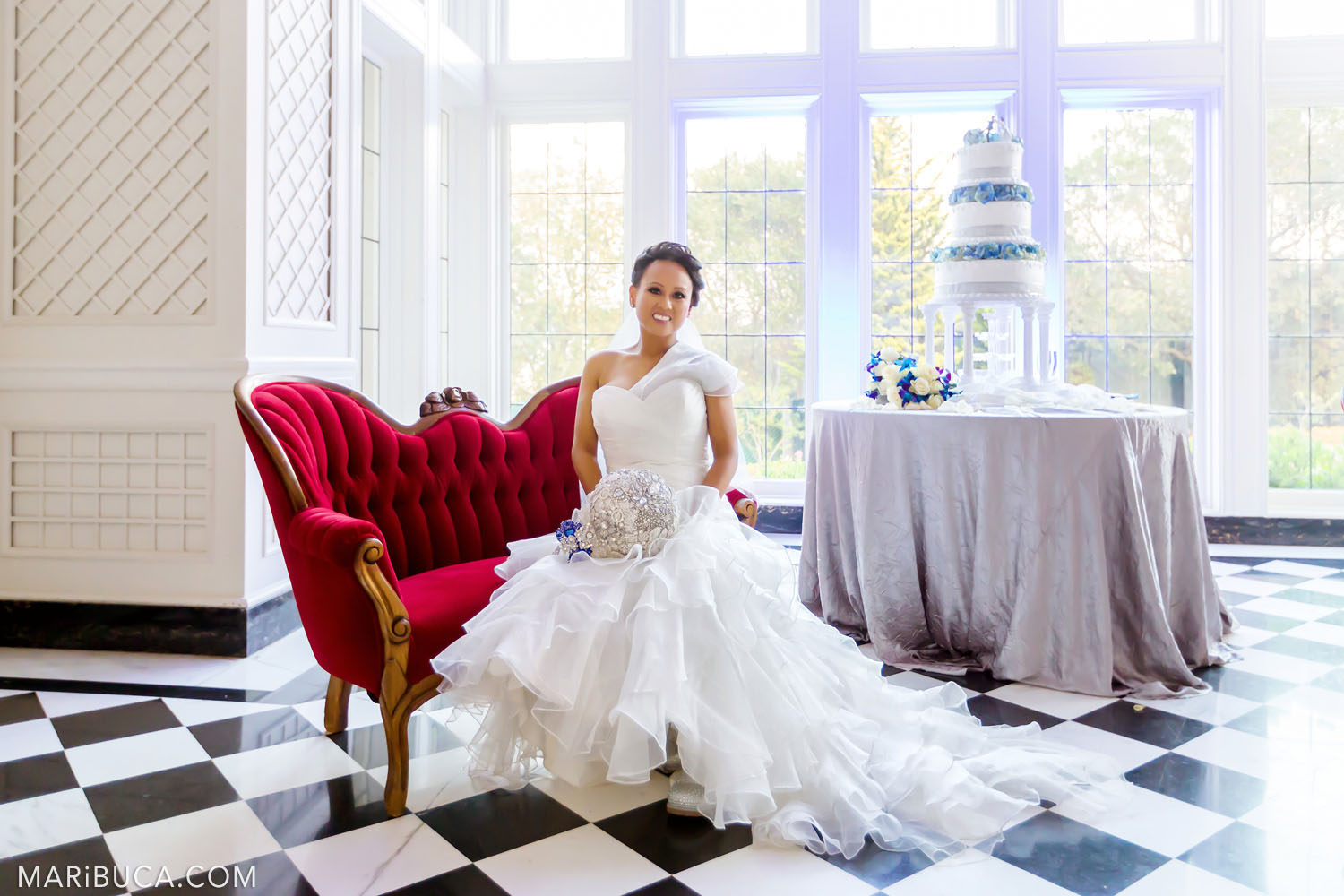 Gorgeous bride sits in the red couch around the Morning Room with big high windows, white walls and white three-stores wedding cake in the Kohl Mansion, Burlingame
