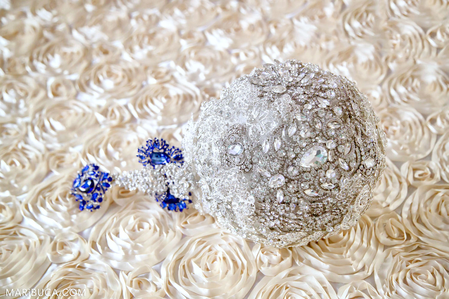 A bridal bouquet with glass and blue stones lies on a textured white tablecloth in the form of roses.